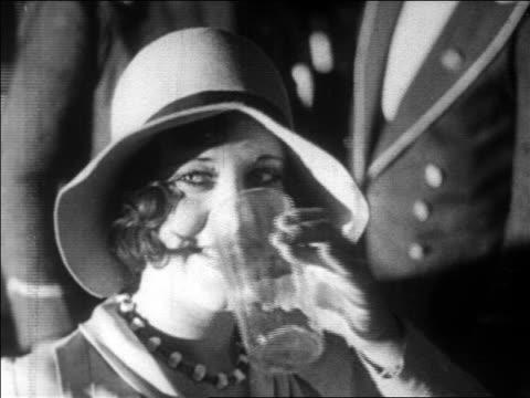 vidéos et rushes de b/w 1928 close up flapper in hat smiling + drinking / newsreel - prohibition