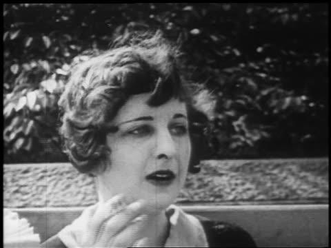 vidéos et rushes de b/w 1925 close up flapper sitting on bench smoking cigarette / newsreel - fumer du tabac