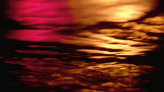 Close up flowing water with orange and pink light reflections from sunset