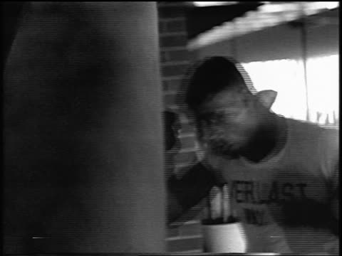 b/w 1956 close up floyd patterson hitting punching bag in training in gym / newsreel - authority stock videos & royalty-free footage