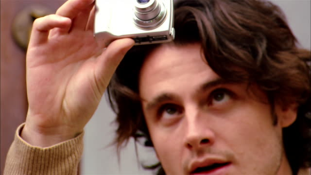 close up focus man taking digital photo/ tilt down man's hands adjusting camera/ brooklyn, new york - digital camera stock videos and b-roll footage
