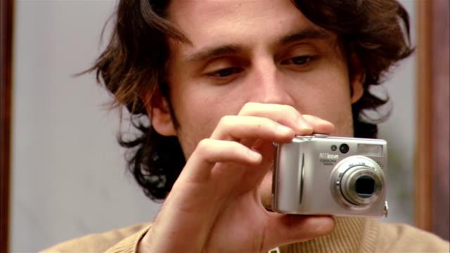 close up focus man taking digital photo/ tilt down man's hands adjusting camera/ brooklyn, new york - digital camera stock videos & royalty-free footage