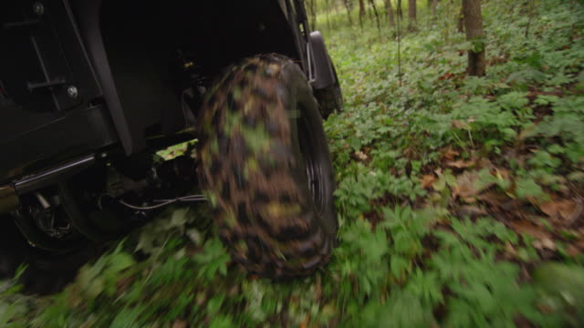 close up following the rear tire of an all terrain vehicle atv driving off road through a muddy forest of trees. - tyre stock videos & royalty-free footage