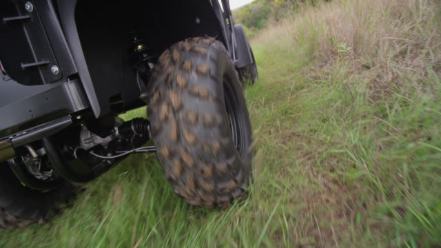 close up following the rear tire of an all terrain vehicle atv driving off road through a grassy muddy field. - quadbike stock videos & royalty-free footage