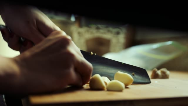 close up footage of a woman chopping the garlic in the kitchen - chopped stock videos & royalty-free footage