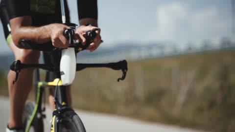 晴れた日に、午前中に自転車をサイクリングする男性トライアスリートの足の映像をクローズアップ。ロードバイク詳細クローズアップショット - active lifestyle点の映像素材/bロール