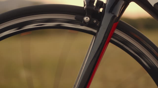 close up footage of male triathlete feet cycling a bicycle in the evening, in a sunny day. road bike detailed close up shot during  sunset - riding stock videos & royalty-free footage