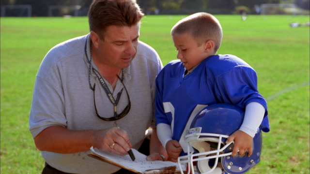 Close up football coach instructing young blond boy wearing football uniform / boy smiling and nodding