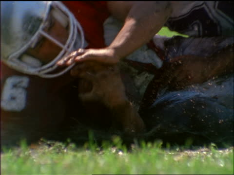 HIGH SPEED close up football player with ball being tackled in muddy wet field