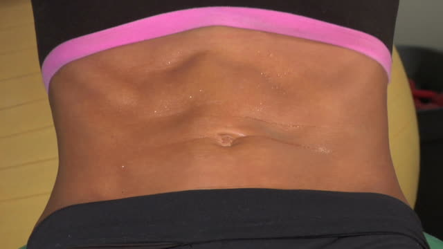 close up for a woman doing crunches - washboard stock videos and b-roll footage