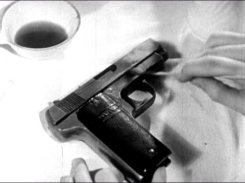 1947 close up forensic scientist applying acid to gun with cotton swab to reveal defaced serial number/ dearborn, michigan - cotton bud stock videos & royalty-free footage