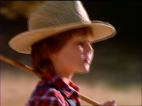 stockvideo's en b-roll-footage met close up freckle-faced boy wearing straw hat + carrying (fishing?) pole - strohoed