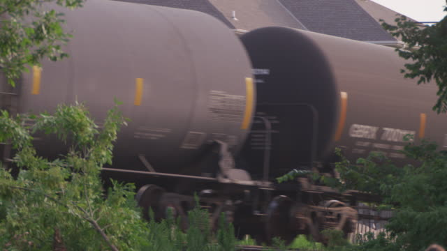 Close up freight train and oil tankers roll past camera in a suburban neighborhood.