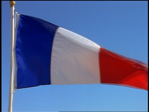 close up French flag blowing in wind / blue sky in background
