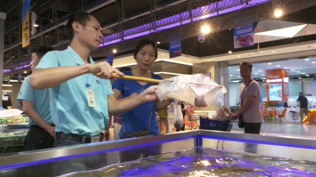Close up fresh prawns sit in netted trays above a water tank in an Alibaba Group Holding Ltd Hema Store in Shanghai China on Tuesday Sept 12 A...