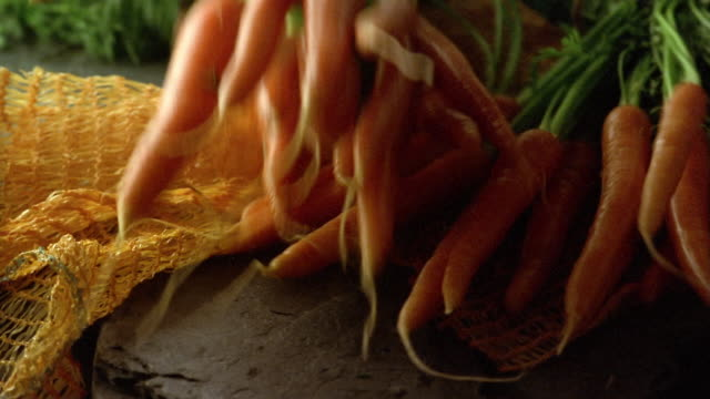 close up freshly washed carrots being tossed onto cheesecloth - still life stock videos and b-roll footage