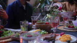 Close up friends and couples passing food on patio mediterranean meal