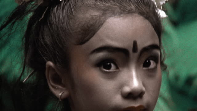 vídeos de stock, filmes e b-roll de tinted close up pan from arm to face of indonesian girl performing traditional dance in native dress /bali - imagem tonalizada