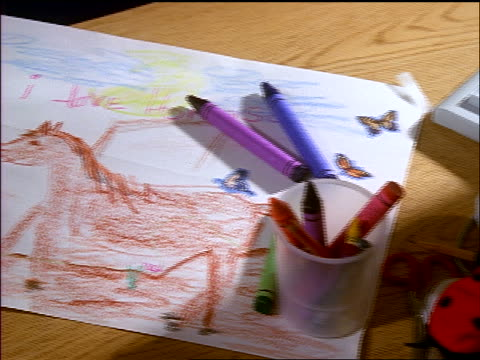 close up pan from child's drawing of horse with crayons laying on it to other drawing being placed on it - pflanzenfressend stock-videos und b-roll-filmmaterial