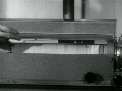 b/w 1956 close up pan from spinning tube to newspaper page printing on early fax machine - fax machine stock videos & royalty-free footage