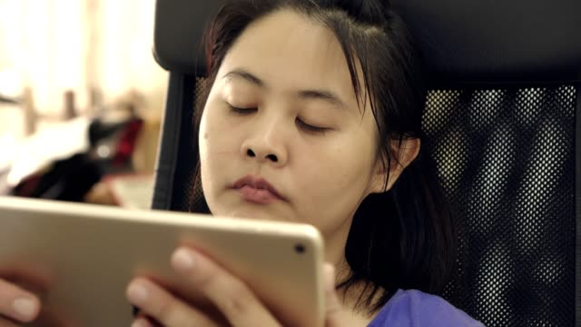 close up front side woman sitting on chair use digital tablet