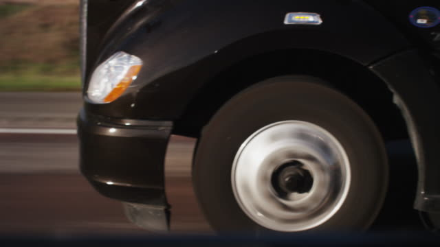 Close up front tires of a semi truck driving down the interstate.