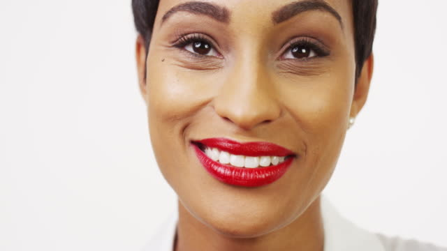 vidéos et rushes de close up front view of pretty black woman with red lipstick smiling and laughing - lèvres