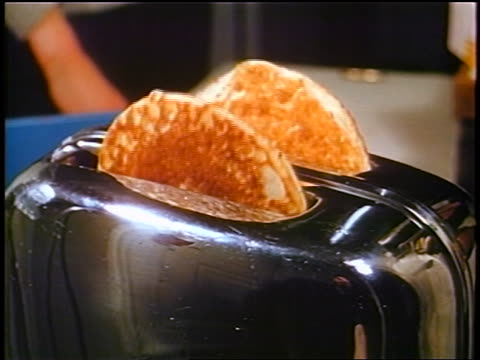 1958 close up frozen pancakes popping up in toaster / woman's hand grabs them / newsreel - toaster appliance stock videos & royalty-free footage