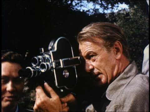 vidéos et rushes de close up gary cooper holding and looking through home movie cam - caméra de cinéma