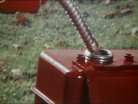 1961 close up gas being poured from can into gas tank of lawnmower / hand closing lid of tank - beccuccio video stock e b–roll