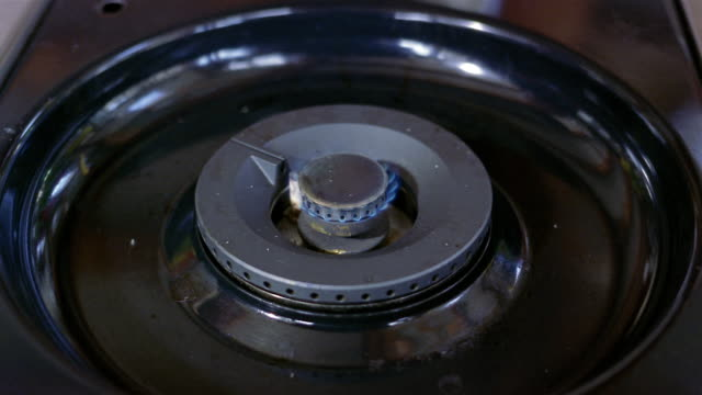 close up gas flame being ignited on range top / flame being lowered / burner turning off - burner stove top stock videos and b-roll footage