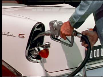 vídeos y material grabado en eventos de stock de 1955 close up gas station attendant's hands filling up chevrolet bel air gas tank located in taillight - echar combustible
