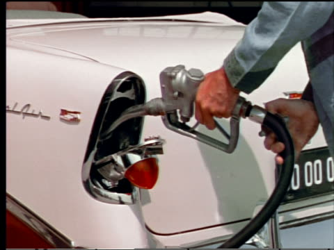 stockvideo's en b-roll-footage met 1955 close up gas station attendant's hands filling up chevrolet bel air gas tank located in taillight - 1955