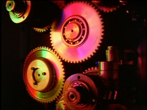 close up gears turning with changing lights