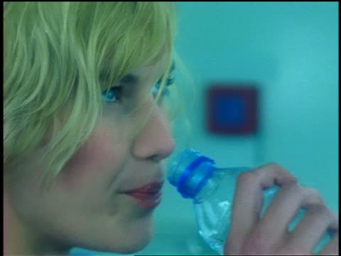 close up gen x blonde woman leaning against gas pump drinking water from bottle + looking at camera - drinking water stock videos & royalty-free footage