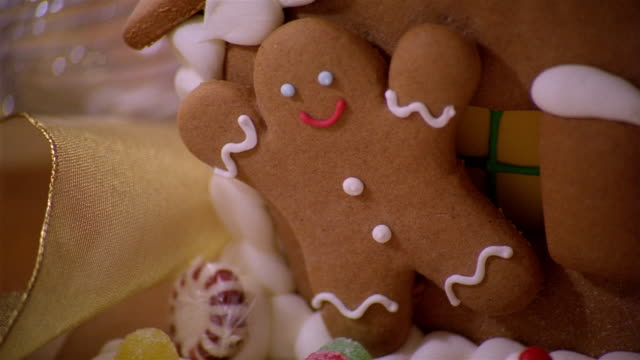 Close up gingerbread man / zoom out gingerbread house on top of table / Christmas tree in background