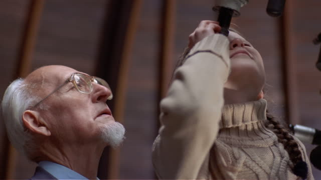 close up girl and grandfather taking turns looking through telescope in observatory - astronomy stock videos & royalty-free footage