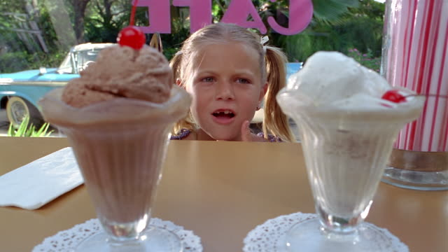 close up girl being served ice cream / taste testing two sundaes / miami, florida - scegliere video stock e b–roll