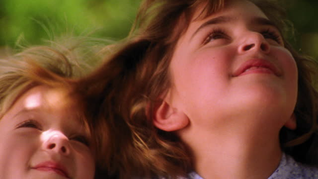 close up girl + blonde girl sitting together on tree swing looking up / wind blowing hair