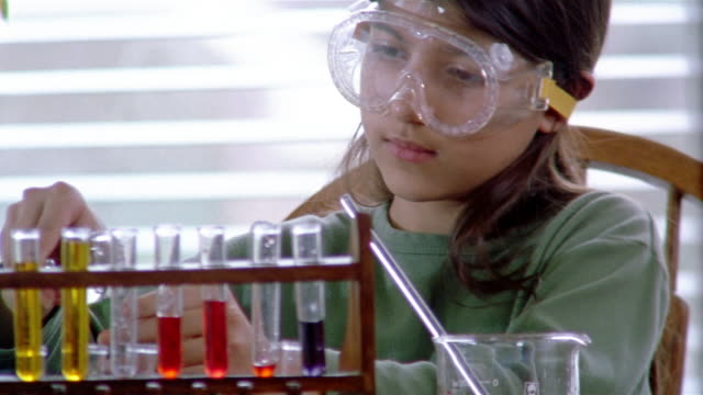 Close up girl conducting experiment in chemistry class