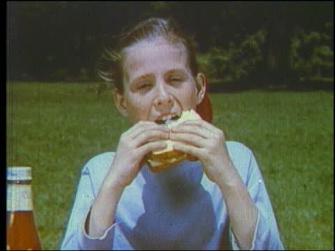 vidéos et rushes de 1960 close up girl eating sandwich outdoors - sandwich