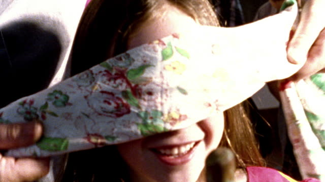 OVEREXPOSED close up girl getting blindfolded + holding stick for pinata at birthday party / kids in background