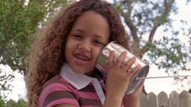 Close up girl holding tin can phone up to ear / talking into can