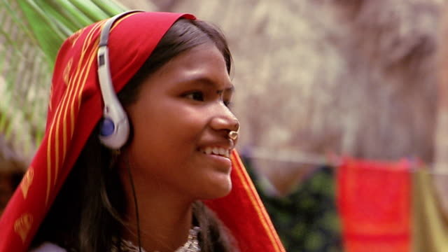 close up girl in traditional dress bobbing to music on headphones / panama - nodding head to music stock videos and b-roll footage