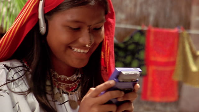 close up girl in traditional dress playing video game / wearing headphones - handheld video game stock videos & royalty-free footage