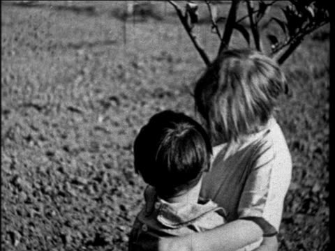 b/w 1927 close up girl kissing other child in lemon orchard outdoors / educational - teenage couple stock videos & royalty-free footage