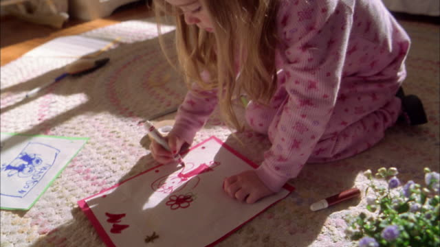 close up girl kneeling on floor and drawing picture w/hearts + flowers - coloring stock videos and b-roll footage
