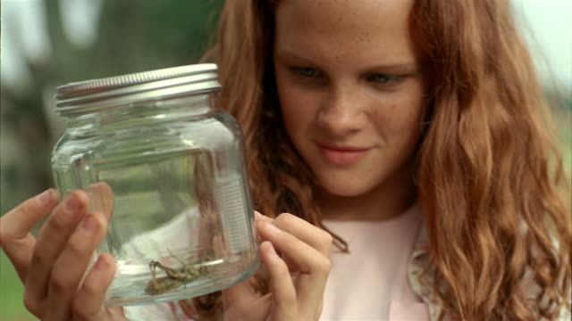 close up girl looking at grasshopper in jar and smiling - pre adolescent child stock videos & royalty-free footage