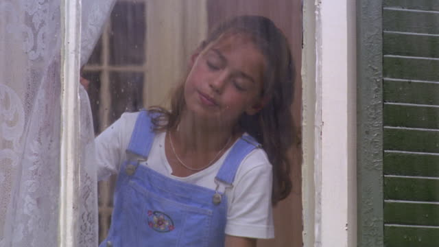 close up girl looking out window at rain with sad expression (shot from outside) - bib overalls stock videos and b-roll footage