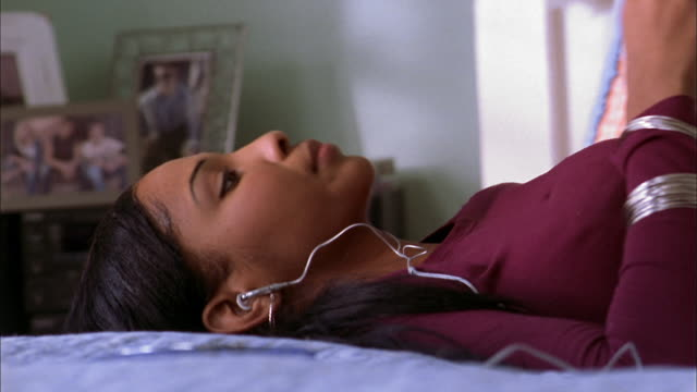 close up  girl lying on bed and listening to music w/earphones - african american culture stock videos & royalty-free footage